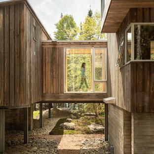 Свежая идея для дизайна: трехэтажный, деревянный, коричневый частный загородный дом среднего размера в стиле модернизм с односкатной крышей и металлической крышей - отличное фото интерьера