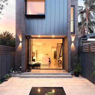 Ispirazione per la facciata di una casa unifamiliare grigia contemporanea a due piani con rivestimento in metallo, tetto piano e copertura in metallo o lamiera