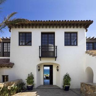 Diseño de fachada blanca, mediterránea, de tamaño medio, de dos plantas, con revestimiento de estuco y tejado plano