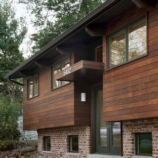 Esempio della facciata di una casa contemporanea a piani sfalsati con rivestimento in legno