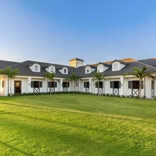 Modelo de fachada de casa beige, contemporánea, grande, de una planta, con revestimiento de hormigón, tejado a cuatro aguas y tejado de metal