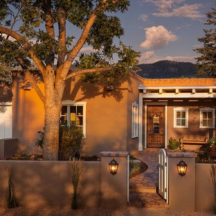 Mid-sized southwest brown one-story stucco flat roof photo in Albuquerque