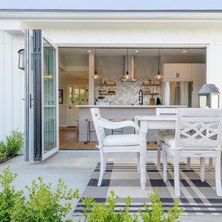 Modelo de fachada blanca, costera, de tamaño medio, de una planta, con revestimiento de madera y tejado de un solo tendido