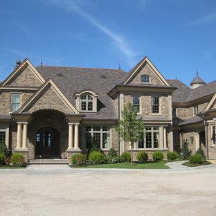 Idee per la facciata di una casa unifamiliare ampia marrone american style a tre piani con rivestimento in pietra, tetto a capanna e copertura in tegole