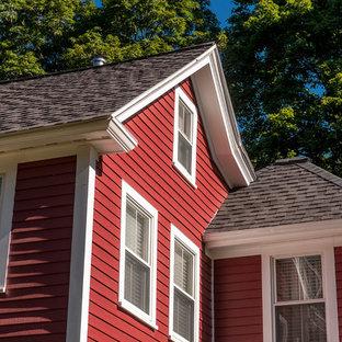 Foto de fachada de casa roja, clásica, grande, de tres plantas, con revestimientos combinados, tejado a dos aguas y tejado de teja de madera
