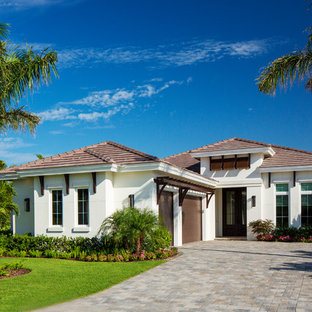 Example of an island style white one-story house exterior design in Miami with a hip roof and a tile roof