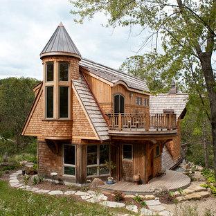 Immagine della villa grande marrone eclettica a tre piani con rivestimento in legno, tetto a capanna, copertura a scandole e tetto marrone