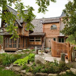 Ispirazione per la facciata di una casa grande marrone eclettica a due piani con rivestimento in legno, tetto a capanna e copertura a scandole