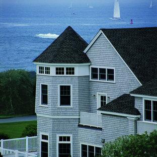 Ejemplo de fachada de casa gris, costera, grande, de dos plantas, con revestimiento de madera, tejado a dos aguas y tejado de teja de madera