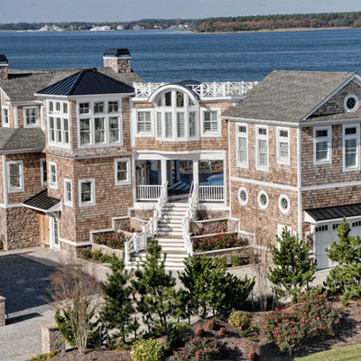 Large coastal three-story wood exterior home idea in Other