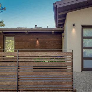 Foto della facciata di una casa unifamiliare marrone moderna a due piani di medie dimensioni con rivestimento in legno, tetto a capanna e copertura in metallo o lamiera
