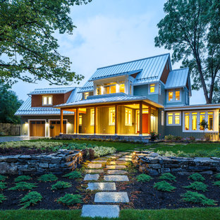 Imagen de fachada de casa verde, de estilo de casa de campo, grande, de dos plantas, con revestimiento de madera, tejado a dos aguas y tejado de metal