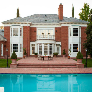 Large elegant red two-story brick exterior home photo in San Diego