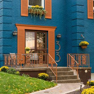 Diseño de fachada azul, ecléctica, grande, de tres plantas, con revestimiento de ladrillo y tejado a dos aguas