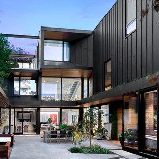 Imagen de fachada de casa negra, contemporánea, grande, de tres plantas, con revestimiento de metal, tejado plano y techo verde