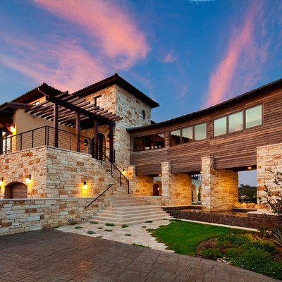Inspiration for a large mediterranean beige three-story stone exterior home remodel in Austin with a shingle roof