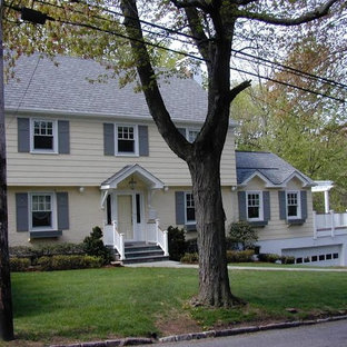 Inspiration for a large timeless yellow two-story wood exterior home remodel in New York with a shingle roof