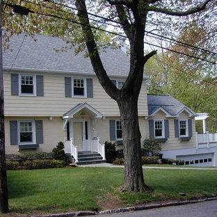 На фото: большой, двухэтажный, деревянный, желтый дуплекс в классическом стиле с двускатной крышей и крышей из гибкой черепицы