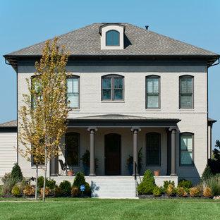 Bild på ett stort vintage hus, med tre eller fler plan, tegel och valmat tak