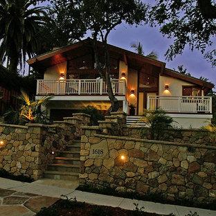 Diseño de fachada beige, vintage, extra grande, a niveles, con revestimientos combinados y tejado a dos aguas