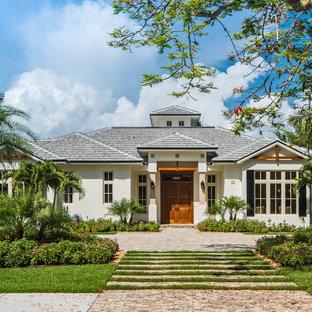 Idée de décoration pour une façade de maison blanche ethnique de plain-pied avec un revêtement en stuc et un toit à quatre pans.