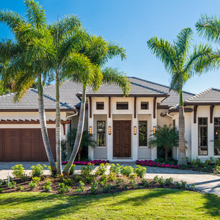 Tropical white one-story stucco house exterior idea in Other with a hip roof