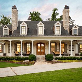 На фото: двухэтажный, кирпичный, белый частный загородный дом в классическом стиле с двускатной крышей, крышей из смешанных материалов и серой крышей
