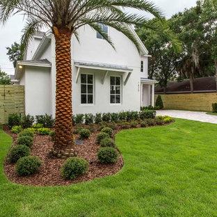 Ejemplo de fachada blanca, campestre, grande, de dos plantas, con revestimiento de estuco