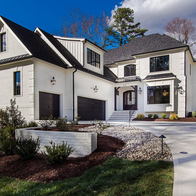 Example of a mid-sized transitional white two-story stucco house exterior design in Raleigh with a mixed material roof