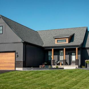 Inspiration pour une grand façade de maison noire nordique de plain-pied avec un revêtement en vinyle, un toit à deux pans et un toit en shingle.