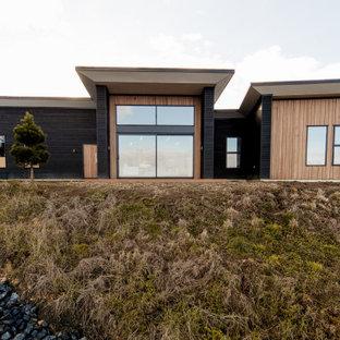 Foto på ett mellanstort funkis svart hus, med allt i ett plan, blandad fasad och tak i metall