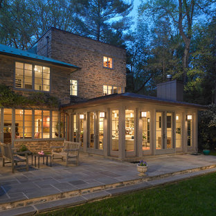 This is an example of a mid-sized traditional grey exterior in Philadelphia with stone veneer.