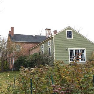 Imagen de fachada verde, de estilo de casa de campo, de tamaño medio, de dos plantas, con revestimiento de ladrillo