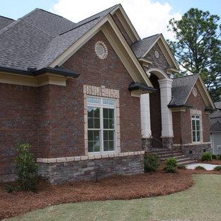 Aménagement d'une grand façade de maison rouge classique à un étage avec un toit à deux pans et un toit en shingle.