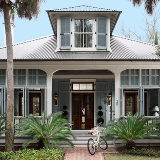 Mid-sized island style blue two-story mixed siding house exterior photo in San Diego with a hip roof and a metal roof