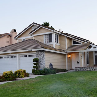 Large southwest beige two-story wood house exterior photo in Los Angeles with a hip roof and a tile roof