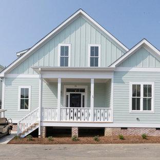 Diseño de fachada verde, campestre, grande, de dos plantas, con revestimiento de aglomerado de cemento y tejado a dos aguas
