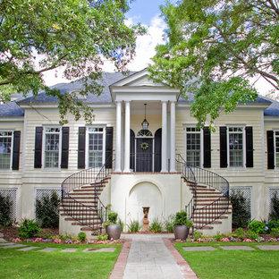 Ejemplo de fachada beige, tradicional, de dos plantas, con tejado a cuatro aguas