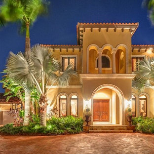Свежая идея для дизайна: большой, двухэтажный, бежевый частный загородный дом в стиле фьюжн с облицовкой из цементной штукатурки, двускатной крышей и черепичной крышей - отличное фото интерьера