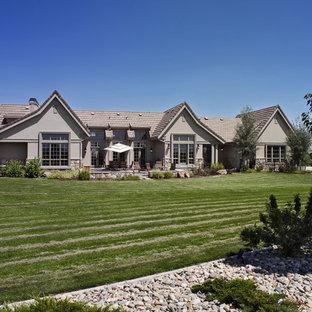 Diseño de fachada de casa gris, bohemia, grande, de una planta, con revestimiento de estuco, tejado a dos aguas y tejado de teja de barro