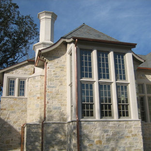 Large elegant beige two-story stone house exterior photo in Houston with a hip roof and a shingle roof