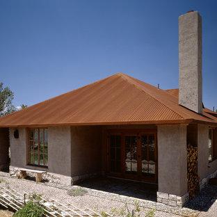 Imagen de fachada gris, rural, de tamaño medio, de una planta, con revestimiento de adobe