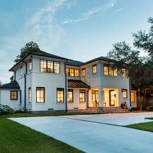 Modelo de fachada de casa blanca, tradicional renovada, grande, de dos plantas, con revestimiento de ladrillo, tejado a cuatro aguas y tejado de teja de madera