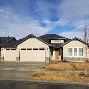 Example of a small trendy beige two-story stucco house exterior design in Boise with a hip roof and a shingle roof