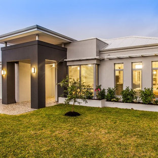 Example of a trendy beige one-story stucco exterior home design in Perth with a hip roof