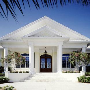 Ejemplo de fachada blanca, mediterránea, grande, de una planta, con revestimiento de estuco y tejado a la holandesa
