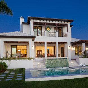 Idee per la facciata di una casa bianca tropicale a due piani di medie dimensioni con rivestimento in stucco e tetto a padiglione