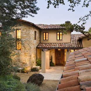 Example of a tuscan two-story stone exterior home design in San Francisco with a tile roof