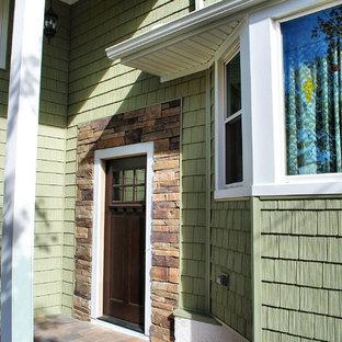 Modelo de fachada verde, clásica, de tamaño medio, a niveles, con revestimientos combinados y tejado a cuatro aguas