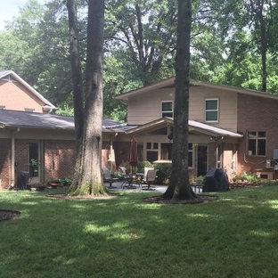 Imagen de fachada de casa blanca, retro, de tamaño medio, a niveles, con revestimiento de ladrillo, tejado a dos aguas y tejado de teja de madera